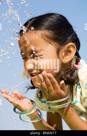 Indian girl splashing water on himself against a blue sky. India - Stock Photo