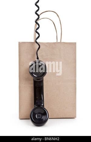 Brown paper shopping bag and telephone with white background - Stock Photo