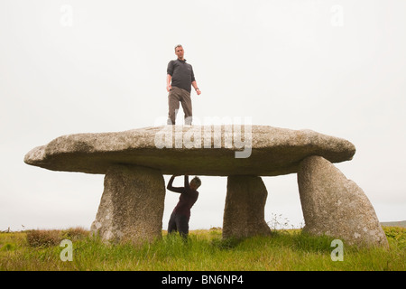 A couple at Lanyon Quoit, an ancient monument near Lands End, Cornwall, UK. - Stock Photo