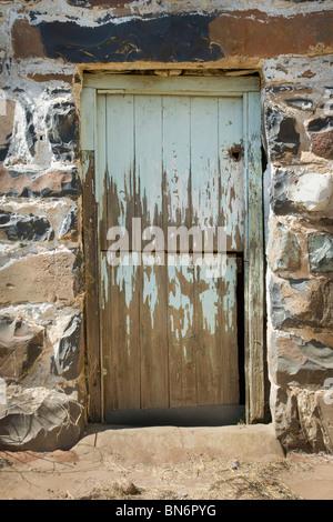 Stone frame with paint peeling from the old wood door. Sunlight on stone frame. Magaliesberg Mountains, Gauteng - Stock Photo