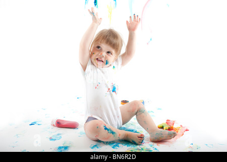 2 year old girl sat covered in paints on white background - Stock Photo