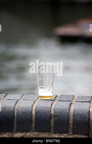 Almost empty pint glass of beer on wall at the Millpond Cambridge showing out of focus punts in background on sunny - Stock Photo