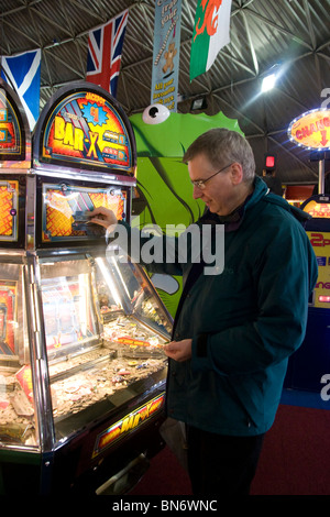 Man Gambling on Penny Falls Machine in Amusement Arcade on Brighton Pier - Stock Photo