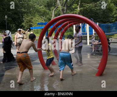 Children cool off in the water area on a hot summer day at the 3rd St. playground in Prospect Park, Brooklyn, NY. - Stock Photo