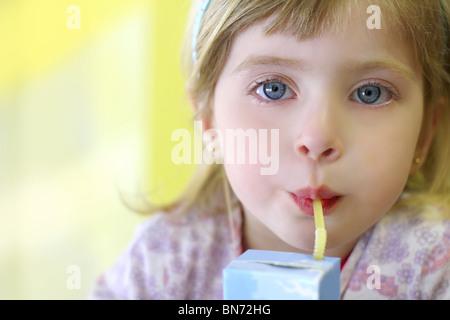 blond little girl drinking straw tetra brick blue eyes - Stock Photo