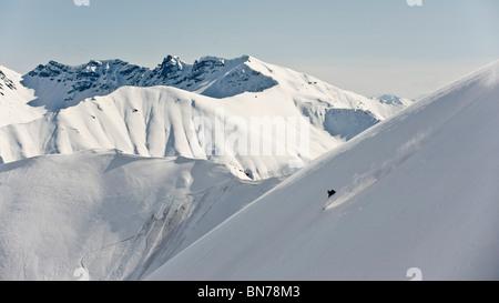 A backcountry skier takes a powder-turn in Hatcher Pass, Alaska - Stock Photo