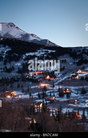 Winter view of hillside homes with lit interiors at dusk with Chugach Mountains in the background, Anchorage, Alaska - Stock Photo