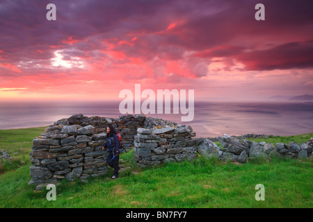 Colorful skies at sunset, and old stone shelter at the island Runde on the Atlantic west coast of Norway. - Stock Photo