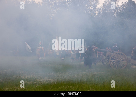 Ramming the charge down the canon's barrel, in the smoke of the previous firing, ready for the next battery exchange. - Stock Photo