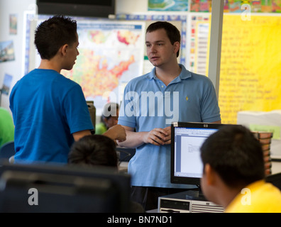 Anglo male high school English teacher talks to student in class. - Stock Photo