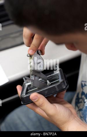 High school boy uses a caliper to take a measurement in freshman engineering class - Stock Photo