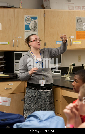 Anglo female high school science teacher explains experiment procedures to class. - Stock Photo