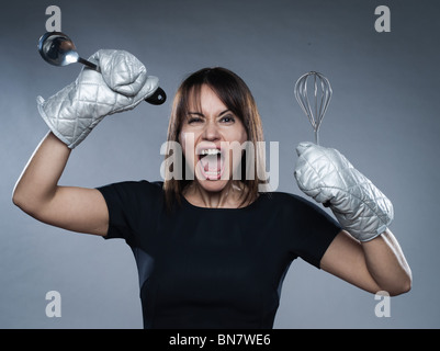 woman strain holding kitchen utensils isolated studio on grey background - Stock Photo