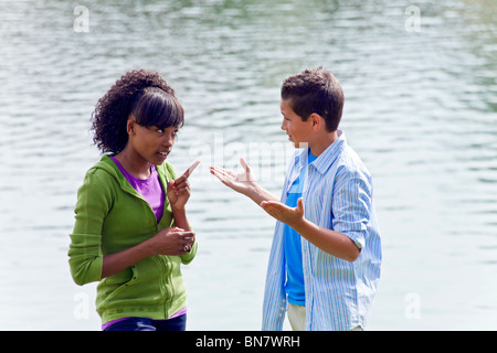 14 15 16 year years old Multi ethnic racial Ethnically diverse teenagers African American Caucasian talking enthusiastic - Stock Photo