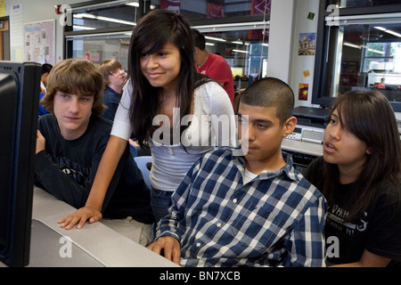 Male and female high school students look at computer monitor during class. - Stock Photo