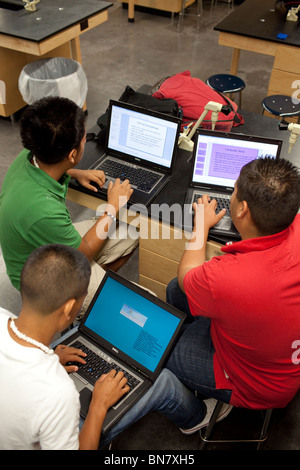 Hispanic high school boys work on assignment together using laptop computers in class. - Stock Photo