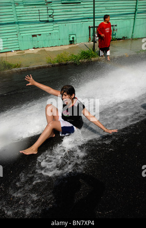 Children in New Haven CT USA cool off in an illegally opened fire hydrant during a summer heat wave with 100 F temps. - Stock Photo