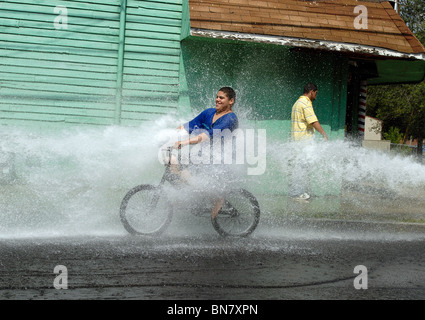 A Young teen rides through the spray of an open fire hydrant during a heat wave in New Haven CT USA where temps - Stock Photo
