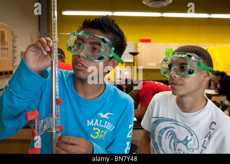 Hispanic high school boys wearing safety goggles measure solution in a graduated cylinder during titration in chemistry - Stock Photo