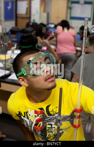 Hispanic male student wearing safety goggles watches solution in graduated cylinder during chemistry class - Stock Photo
