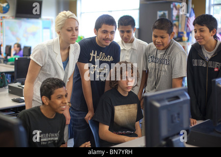 Female Anglo high school teacher and male Hispanic students look at fellow student's computer screen during class - Stock Photo