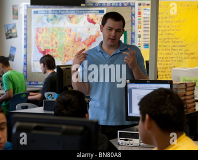 Anglo male high school English teacher gestures while talking to student in class. - Stock Photo