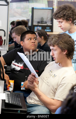 High school boys look at instructions together during class. - Stock Photo