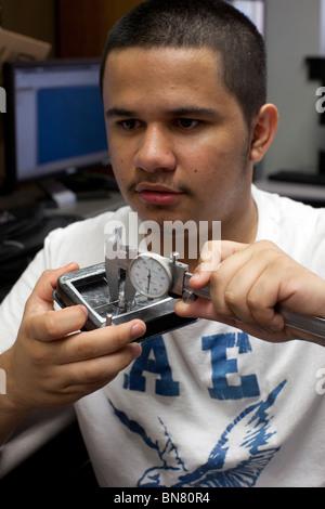 Hispanic high school boy uses a caliper to take a measurement in freshman engineering class - Stock Photo