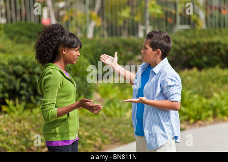 California Multi ethnic racial Ethnically diverse group teenagers African American teens talking enthusiastic conversation - Stock Photo