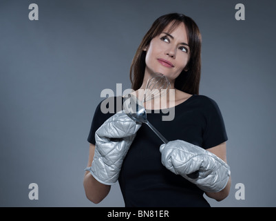one caucasian woman thinking holding kitchen utensils isolated studio on grey background - Stock Photo