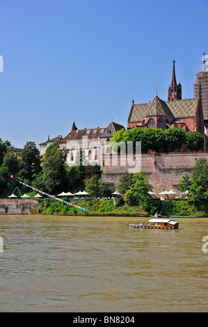 Cable ferry across the river Rhine in Basel (Bale) Switzerland, with Basel Munster (cathedral) in the background. - Stock Photo
