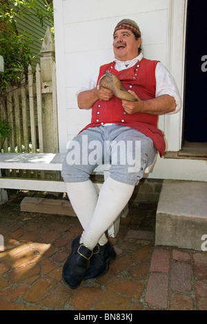 A costumed shoemaker holds the wooden form for 18th-century footwear that he makes and wears in historic Colonial - Stock Photo