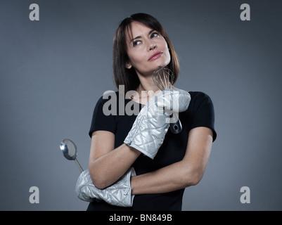 one  woman thinking holding kitchen utensils isolated studio on grey background - Stock Photo