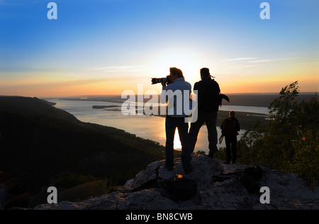 Silhouettes of photographers on top of Zhiguli mountains at sunset over Volga river - Stock Photo