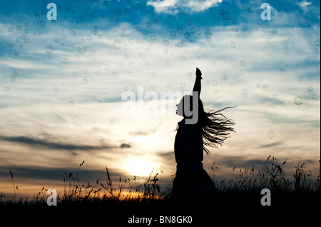 Young Girl energetically having fun jumping and catching bubbles at sunset. Silhouette - Stock Photo