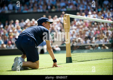 Ball boy waits by the net on centre court during the Wimbledon Tennis Championships 2010 - Stock Photo