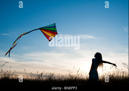 Young Girl having fun flying a multicoloured kite in the English countryside. Silhouette - Stock Photo