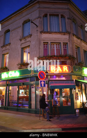 A bar with glowing neon signs at dusk, Verdun, France - Stock Photo