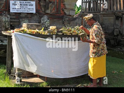 Balinese priest, or holy man collecting money left in offerings made by worshippers, Pura Penataran Sasih Temple, - Stock Photo