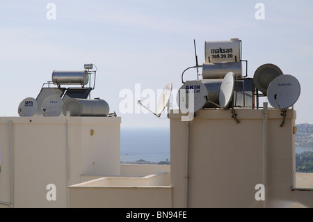 Solar panels and telecommunication satellite dishes on a rooftop in Turkey - Stock Photo