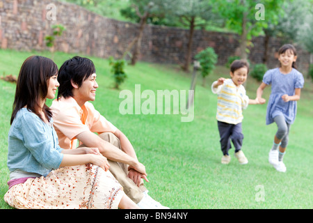 Parents sitting and children running on lawn smiling - Stock Photo