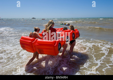 Three girls taking part in the annual Brighton Paddle Round The Pier race with their inflatable car craft. - Stock Photo
