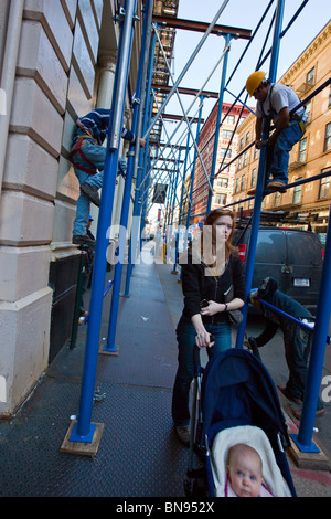 Woman with baby stroller, men assembling scaffolding, Tribeca, New York - Stock Photo