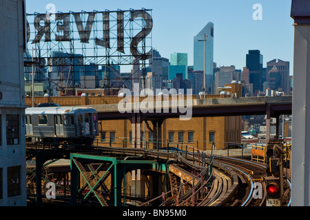 Train above ground on the 7 subway line in Queens, New York - Stock Photo