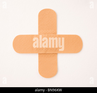 Medical cross made from two plasters isolated on white - Stock Photo