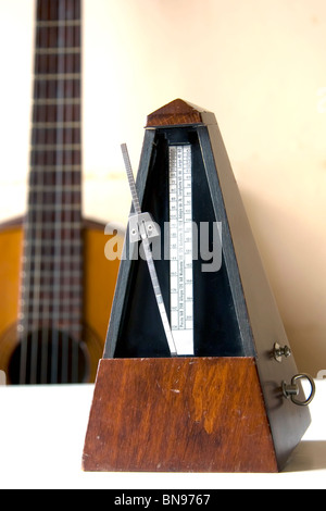 Old metronome over white table with guitar behind (vertical photo) - Stock Photo