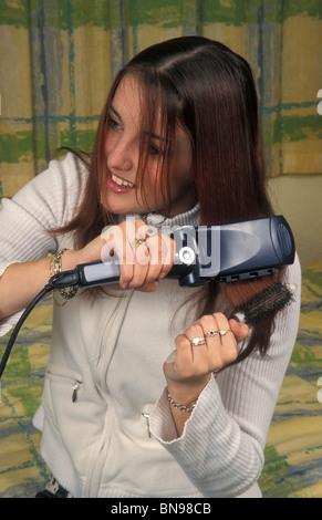 Teenage girl straightening hair - Stock Photo
