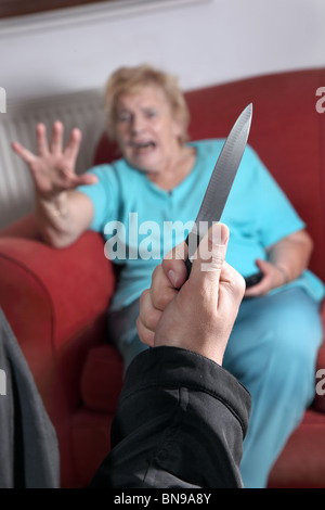 Knife pulled as terrified elderly woman looks towards the attacker - Stock Photo