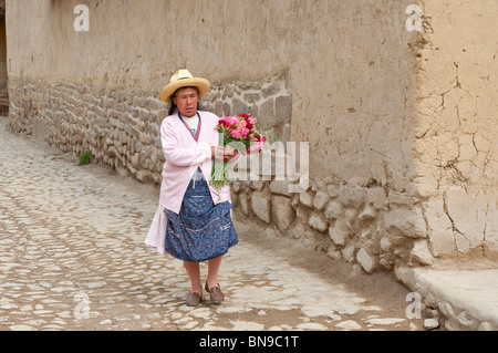 Lady in traditional peruvian dress walking on the street in Ollantaytambo, Peru, South America. - Stock Photo