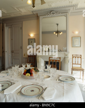 Place settings on table with white cloth in dining room with antique gray painted mirror above fireplace and lighted - Stock Photo